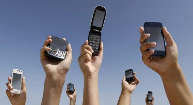 personne tenant des téléphones portables en l'air
