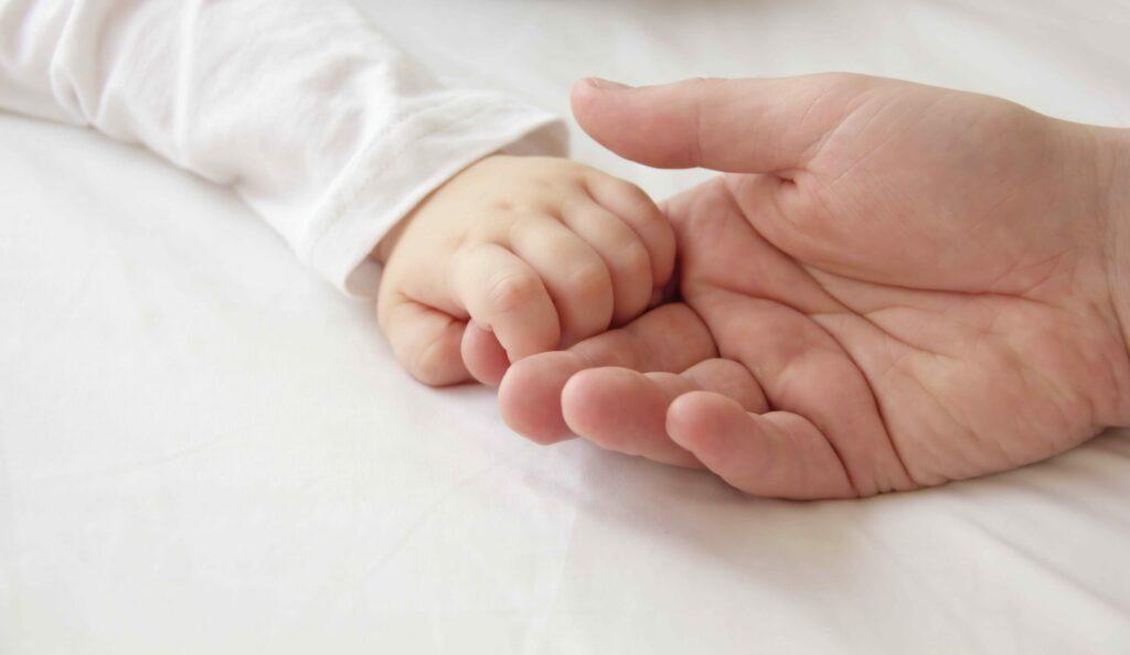 Une main de bébé tenant une main d'adulte