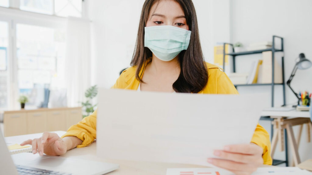 Une femme portant un masque et lisant un document