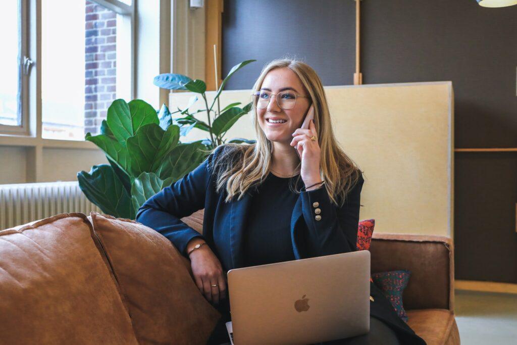 Une femme souriante au téléphone devant son ordinateur