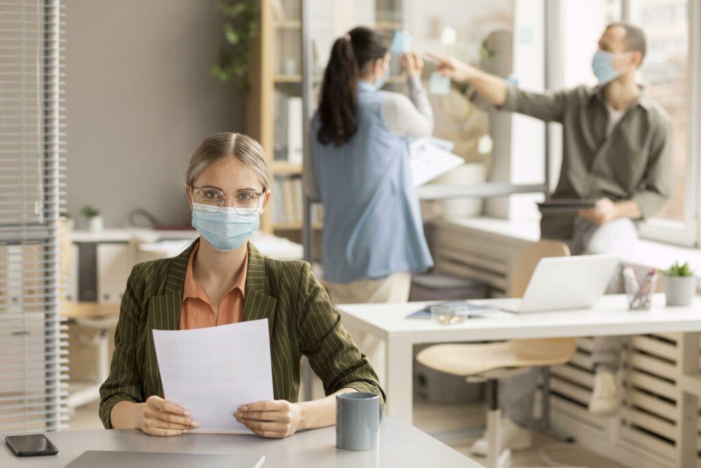 des employés portant des masques au bureau
